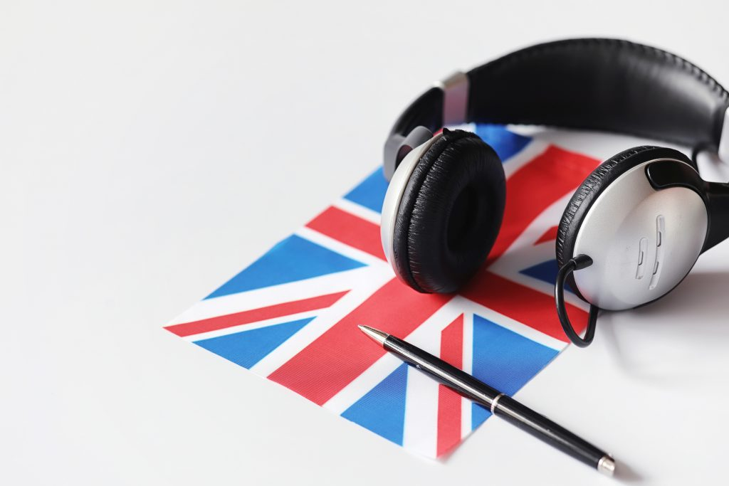 a British Union Jack flag underneath some headphones which someone is using to listen to the British accent