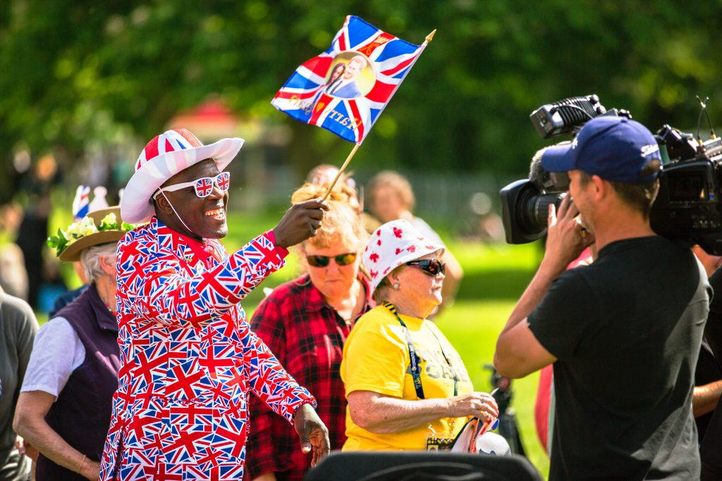 man in a British union jack suit smiling for the cameras